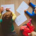 enfants qui dessinent allongés sur le sol
