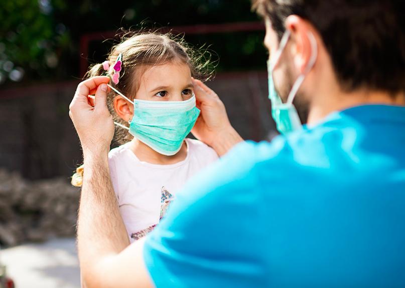 Un père qui met un masque à son enfant