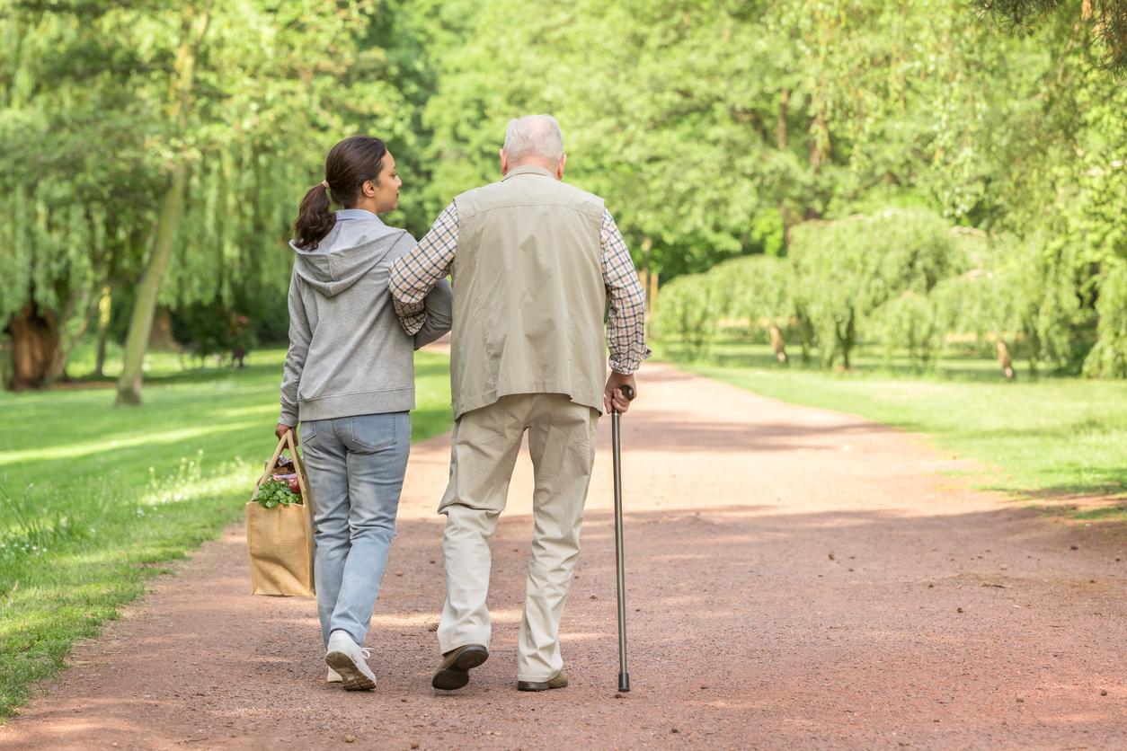 Une personne âgée qui marche en tenant le bras d'une femme plus jeune.