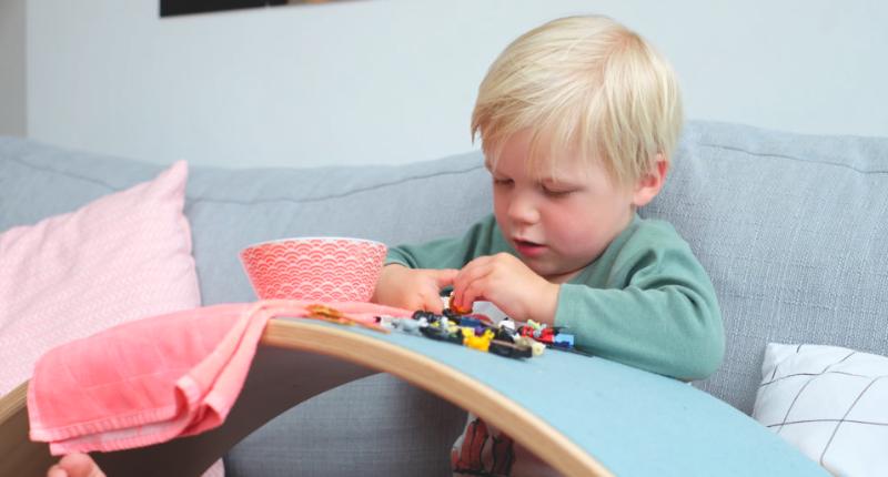Un enfant qui utilise la planche Wobbel comme une table pour jouer.