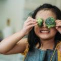 Une enfant tient deux fleurons de brocolis devant ses yeux en souriant.