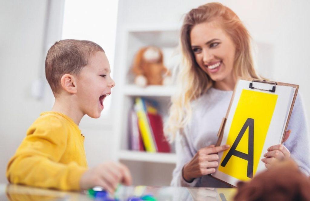 Une orthophoniste travaille avec un enfant sur la lettre A
