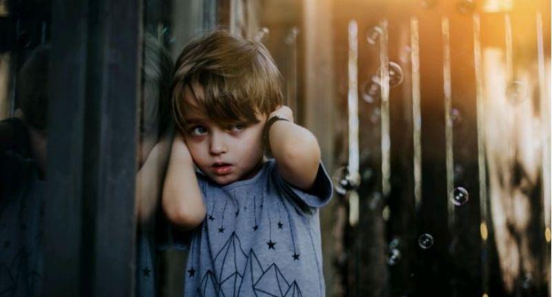 Petit garçon qui se bouche les oreilles avec ses mains.