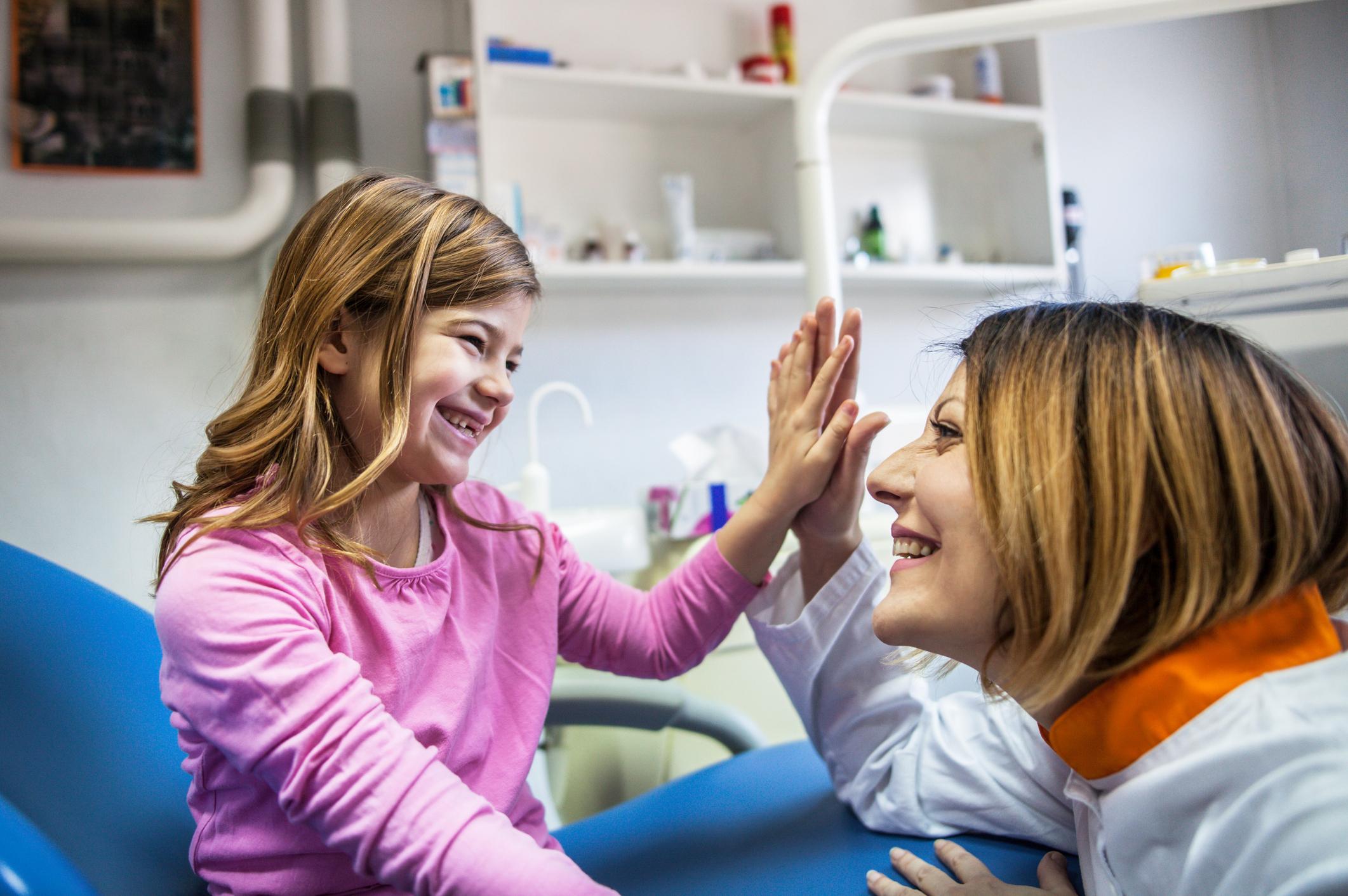 Enfant qui sourit et tape dans la main d'un docteur.