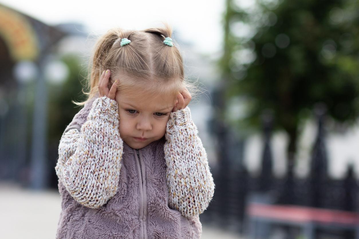 Enfant hypersensible qui se tient la tête avec les mains