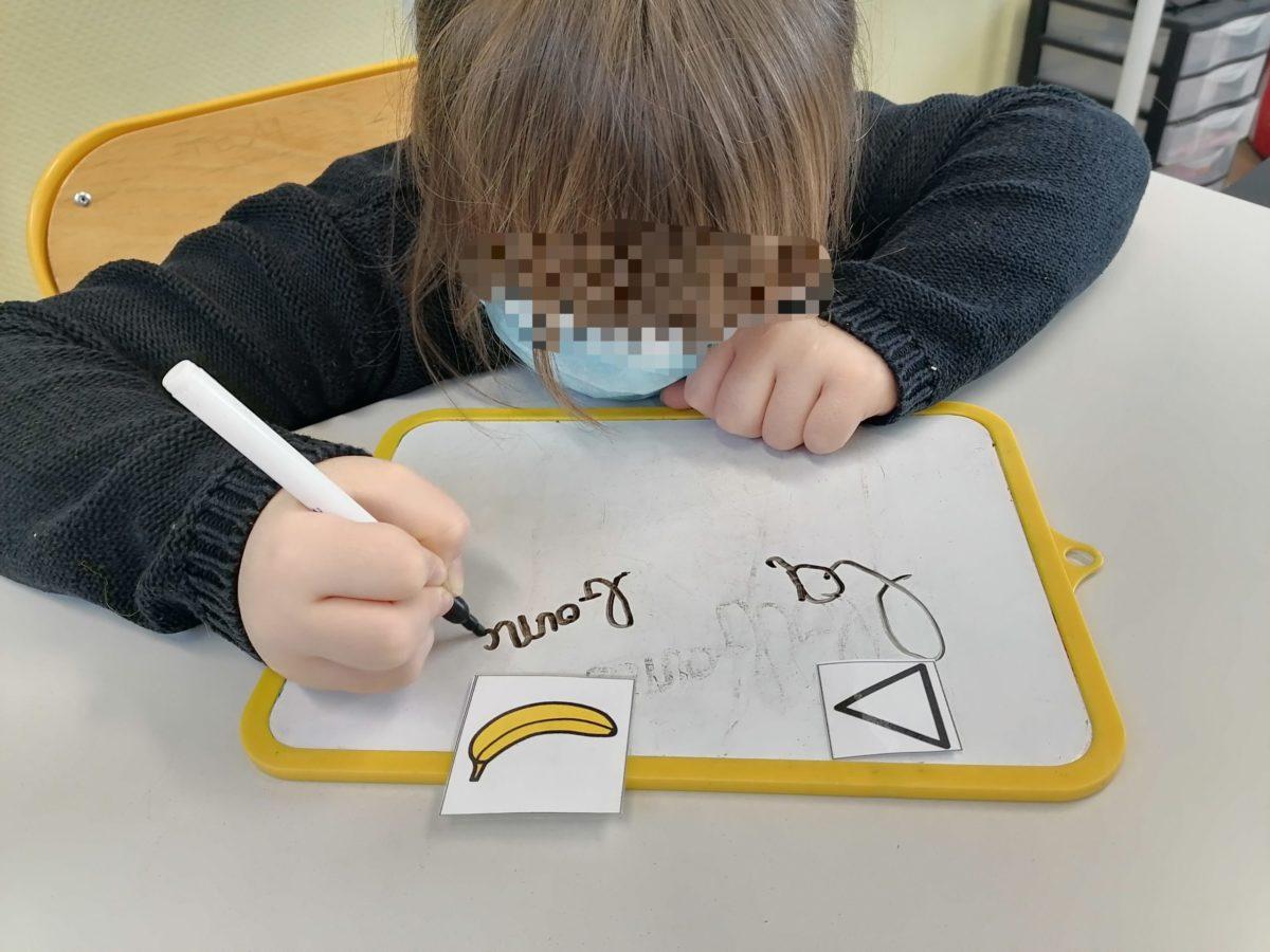 Un enfant écrit des mots à partir de pictogrammes