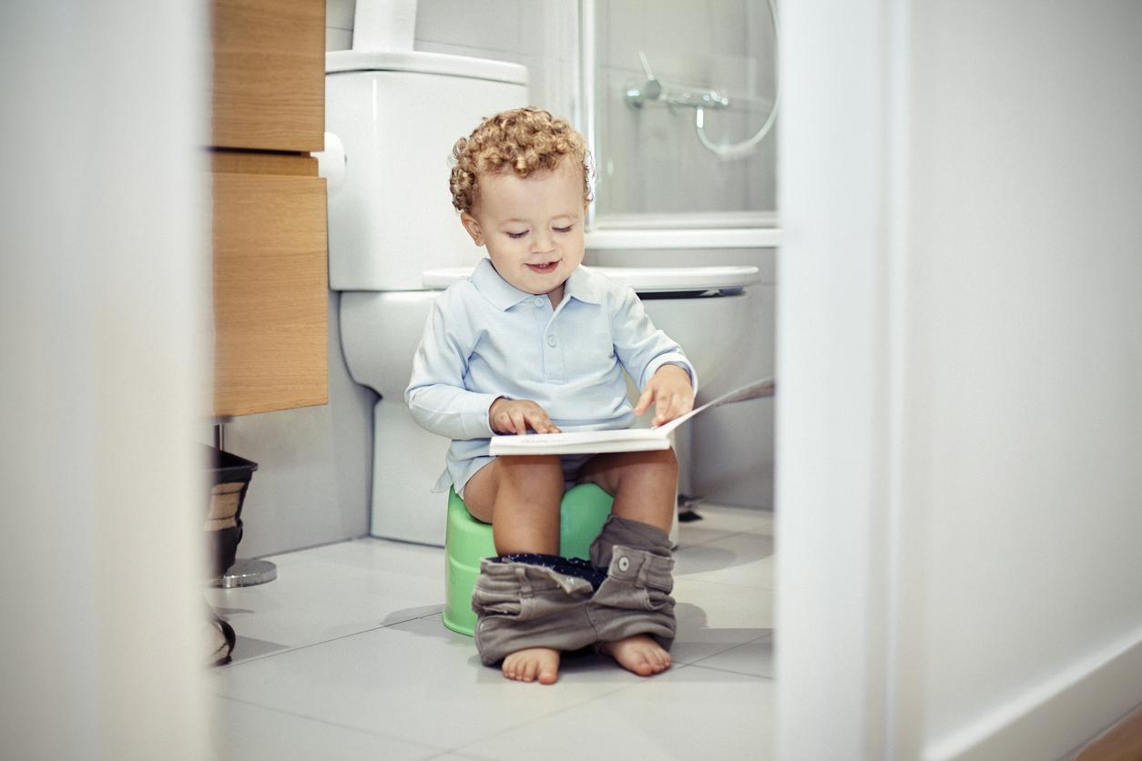 Enfant sur un pot d'apprentissage avec un livre dans les mains