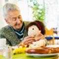 Une personne âgée tient une poupée empathie