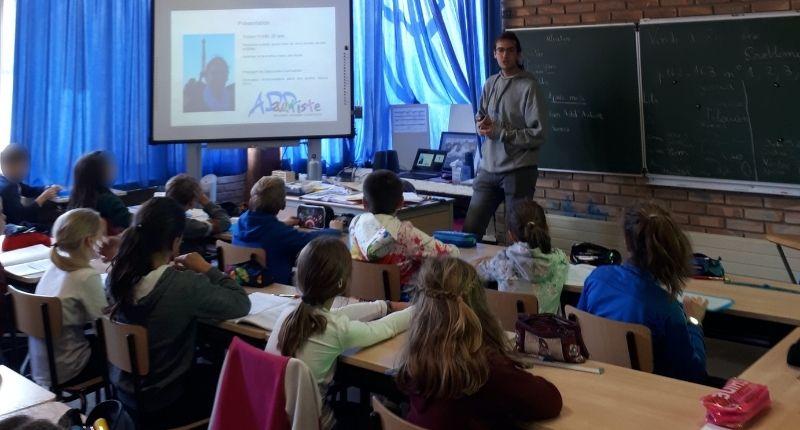 Tristan qui fait de la sensibilisation devant une classe à l'école primaire.