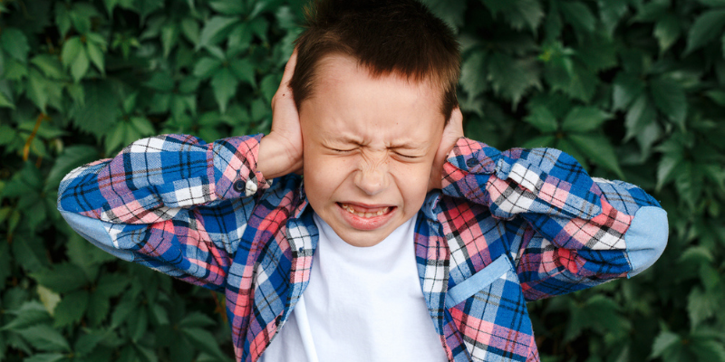 Un enfant se bouche les oreilles en grimaçant