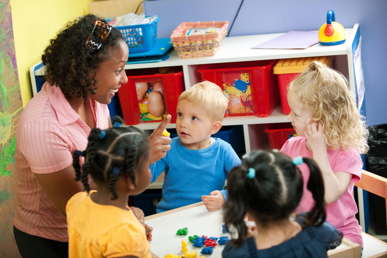 De jeunes enfants apprennent les nombres avec leur enseignante de maternelle.