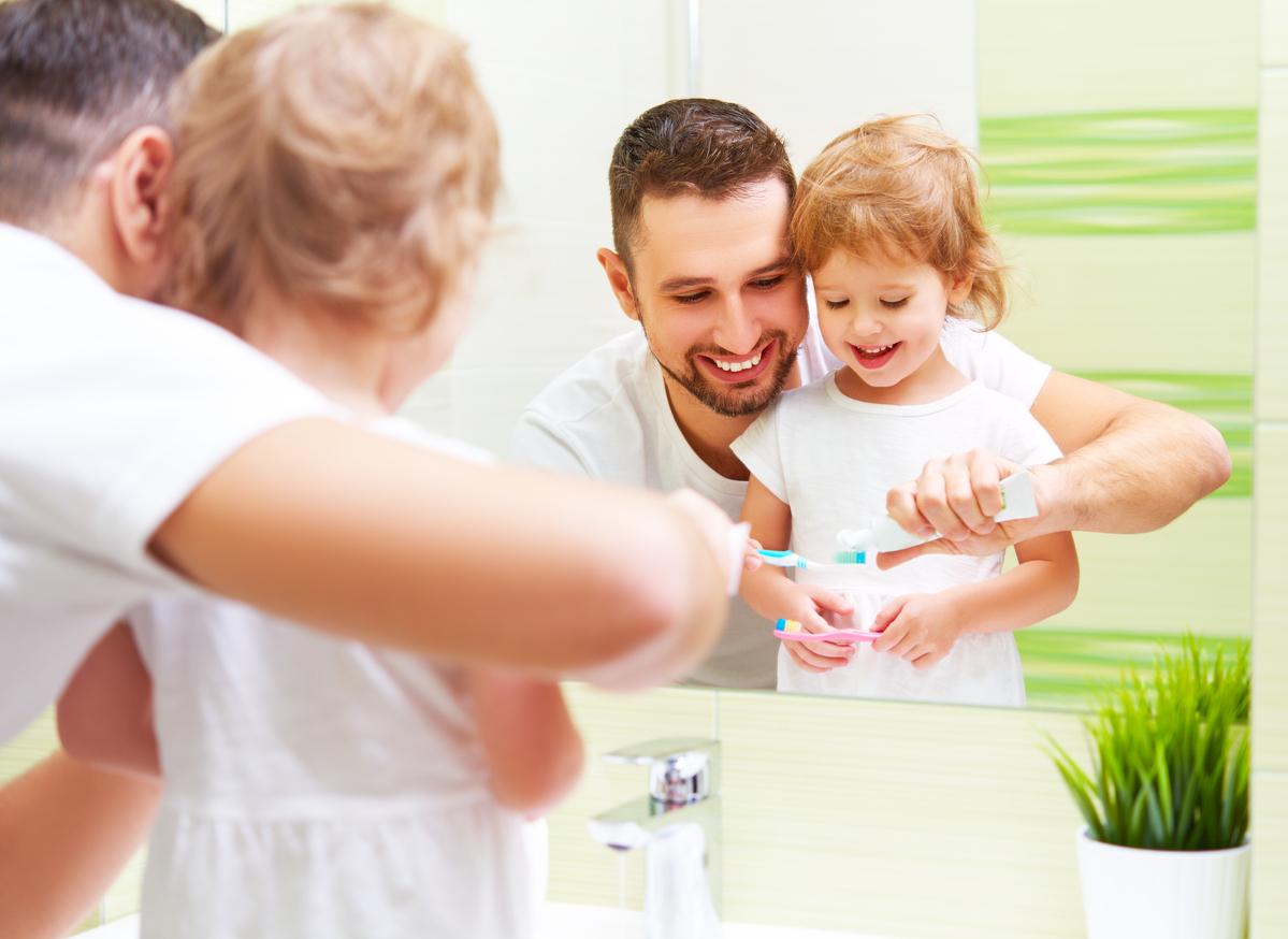 Enfant qui se brosse les dents avec son père devant le miroir.