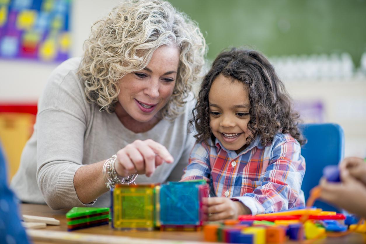 Une enseignante avec un enfant pendant des apprentissages.