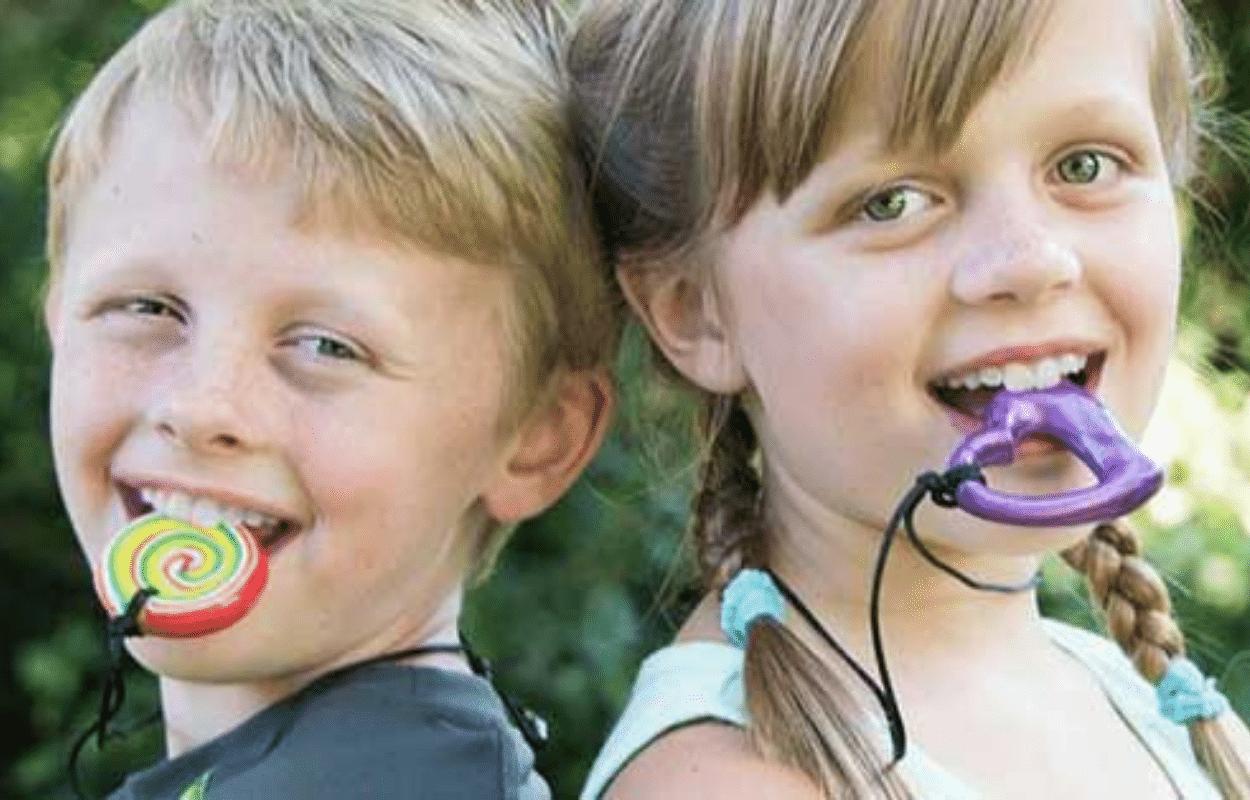 Deux enfants dos à dos avec des colliers Chewigem