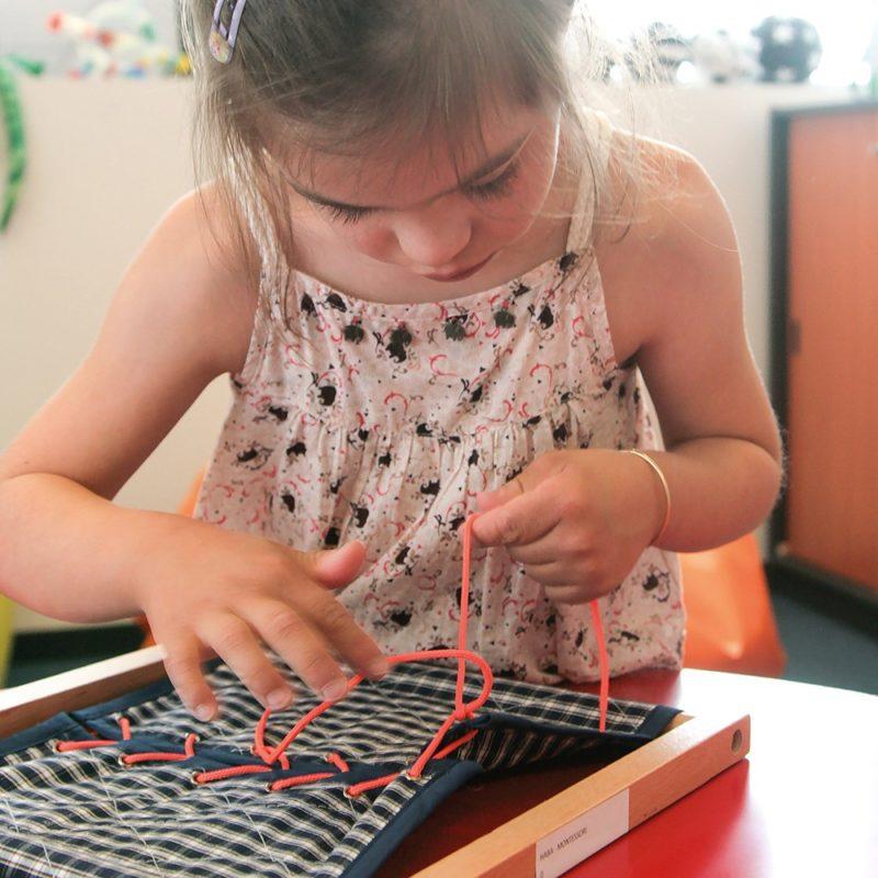 Une enfant entraîne sa motricité avec des lacets