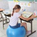 Une élève est assise sur une Sitting Ball