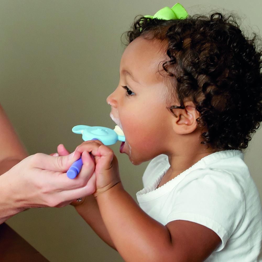 Solution troubles de l'oralité : Une enfant reçoit de la nourriture dans un embout z-vibe en forme de tête de souris.