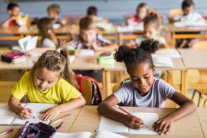 Enfants assis en salle de classe à école