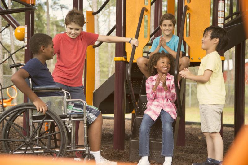Un groupe d'enfants dont un enfant en fauteuil roulant qui discute et rient pendant la récréation.