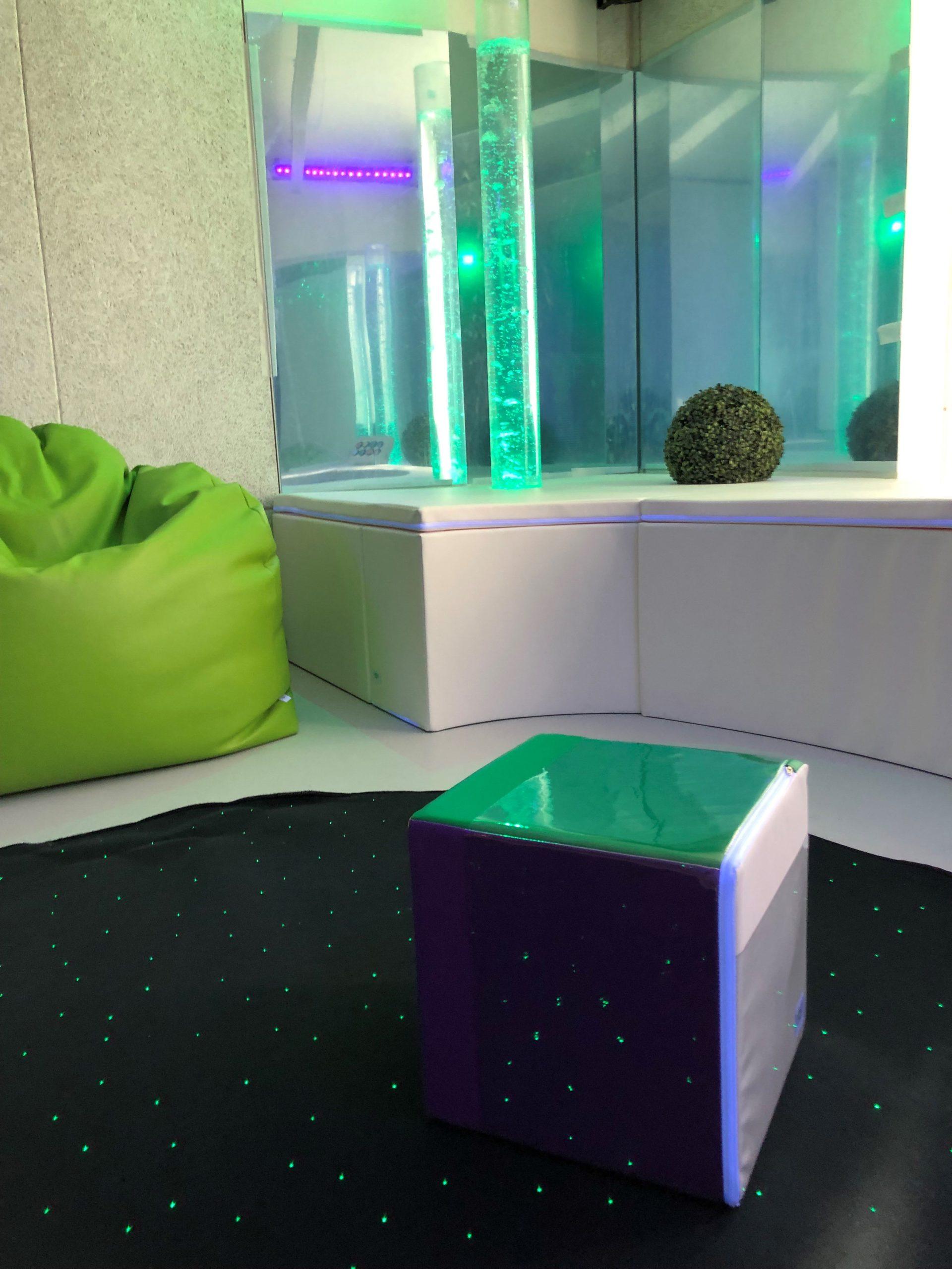 Zoom sur les détails de la salle sensorielle : pouf géant, colonne à bulles et un cube